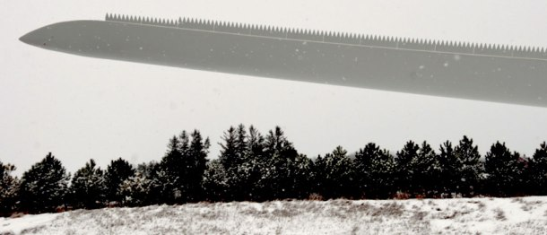 Rick Matthews panoramic image of an industrial wind turbine blade at a truck stop on the 401 highway. (Above) A closer image also by Matthews, reveals a saw-toothed cutting edge on the blade.